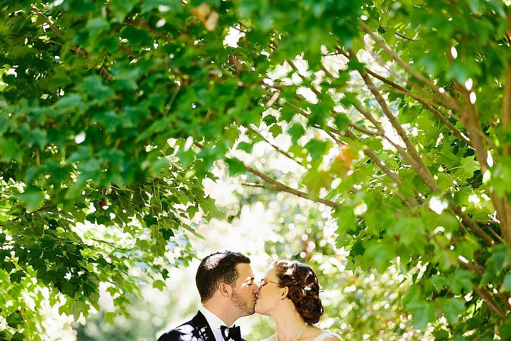Bride and groom kiss under tree canopy