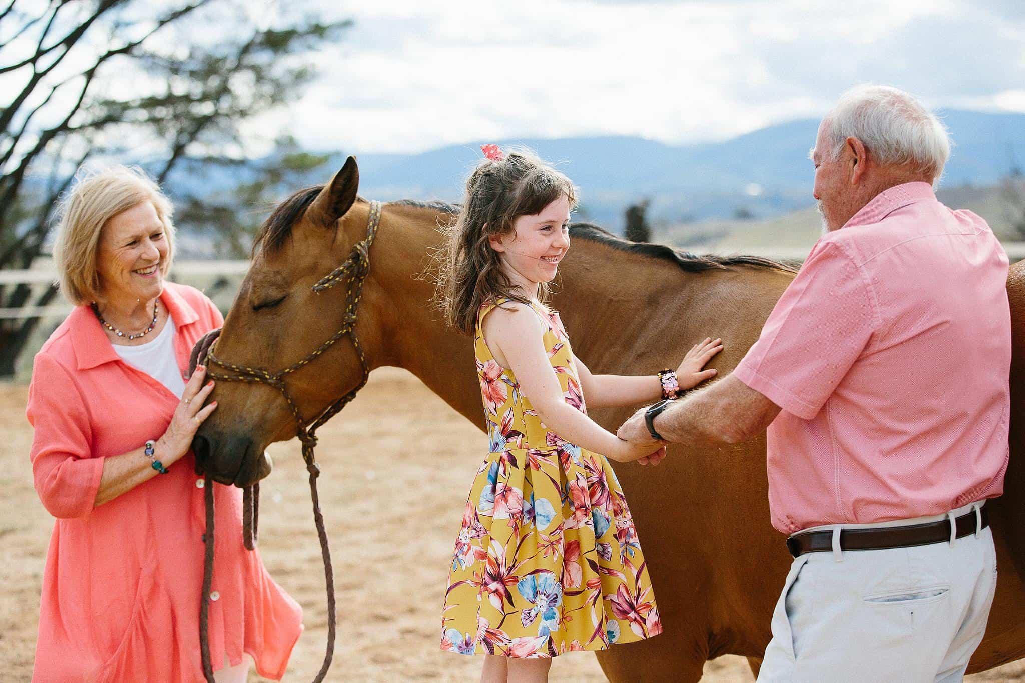 Grandparents help grandchild onto horse