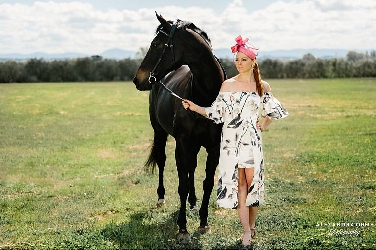 Woman holds horse in fashion dress